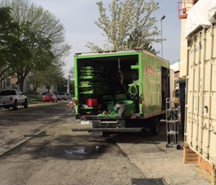 The back of a SERVPRO truck opened, loaded with many equipment.